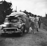 Ron Church – Sunset Beach, Tourists (Women) Looking at Surfboards on Car, circa 1963